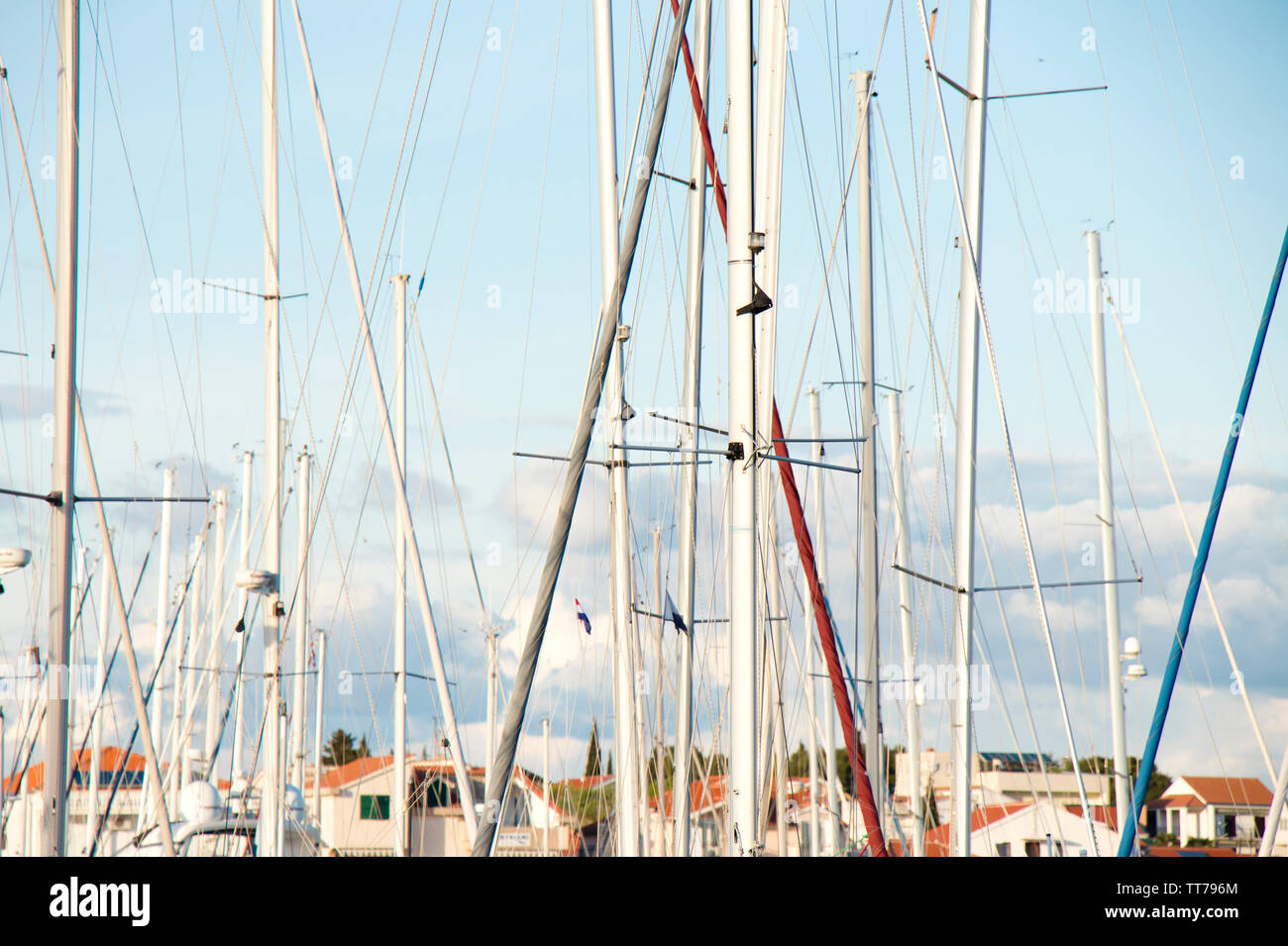 Masts of sailing boats fleet anchored in marina with town houses in the background - Stock Image