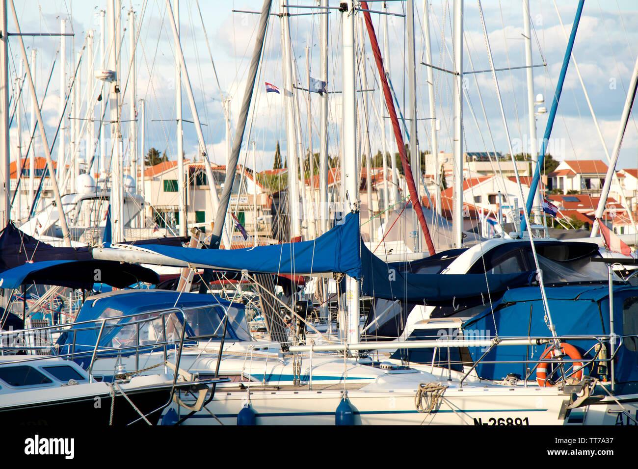 Vodice, Croatia - April 30, 2019: Sailing boats and fast boats anchored in marina in Adriaic sea - Stock Image