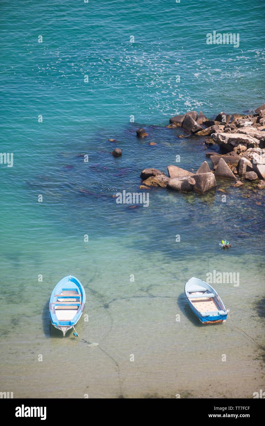 High angle view of two boats floating on blue water. - Stock Image