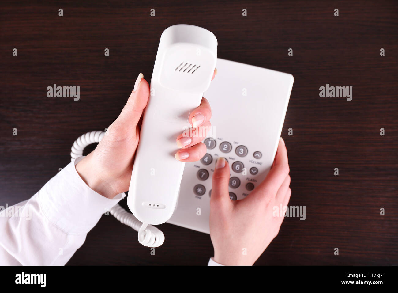 Female hand holding phone receiver and dialing number on wooden background - Stock Image