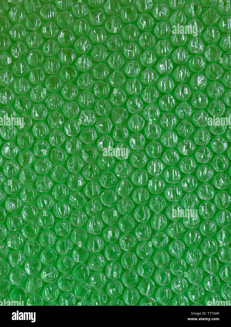 Cellophane and plastic background. The texture of old plastic's packing with balls. Image green and white tones. - Stock Image