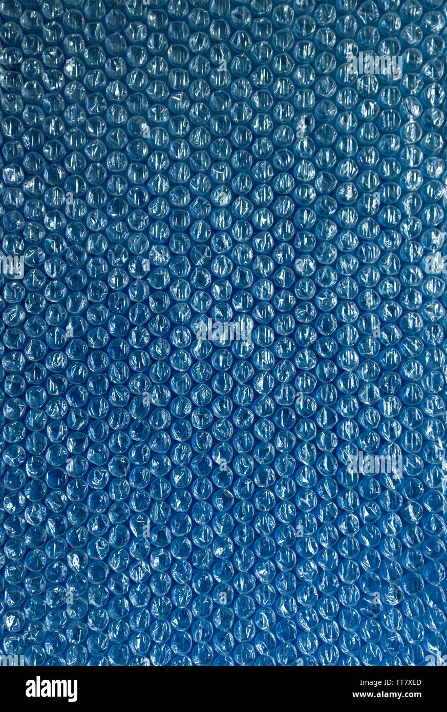 Cellophane and plastic background. The texture of old plastic's packing with balls. Image blue and white tones. - Stock Image