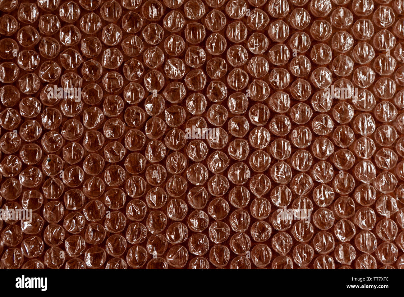 Cellophane and plastic background. The texture of old plastic's packing with balls. Image with effect brown and white tones. - Stock Image