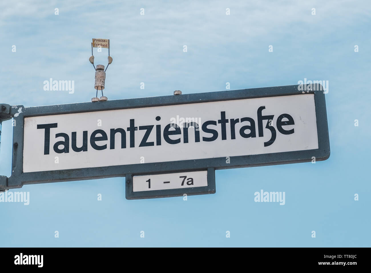 Berlin, Germany - june 2019: Street sign of the Tauentzienstrasse, with miniature model protesting for freeedom of the press (german: Pressefreiheit) - Stock Image