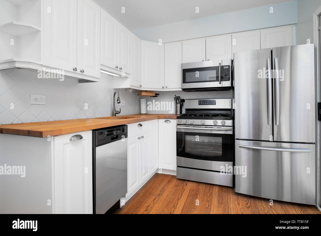 A Small Kitchen With Stainless Steel Appliances White