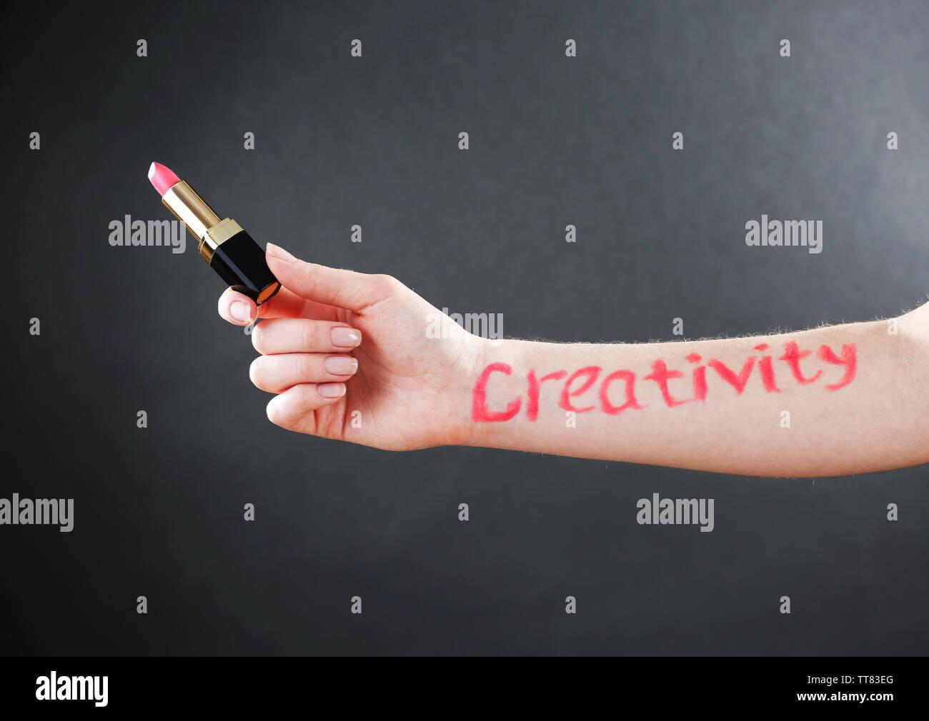 Word creativity written on female hand on black background - Stock Image