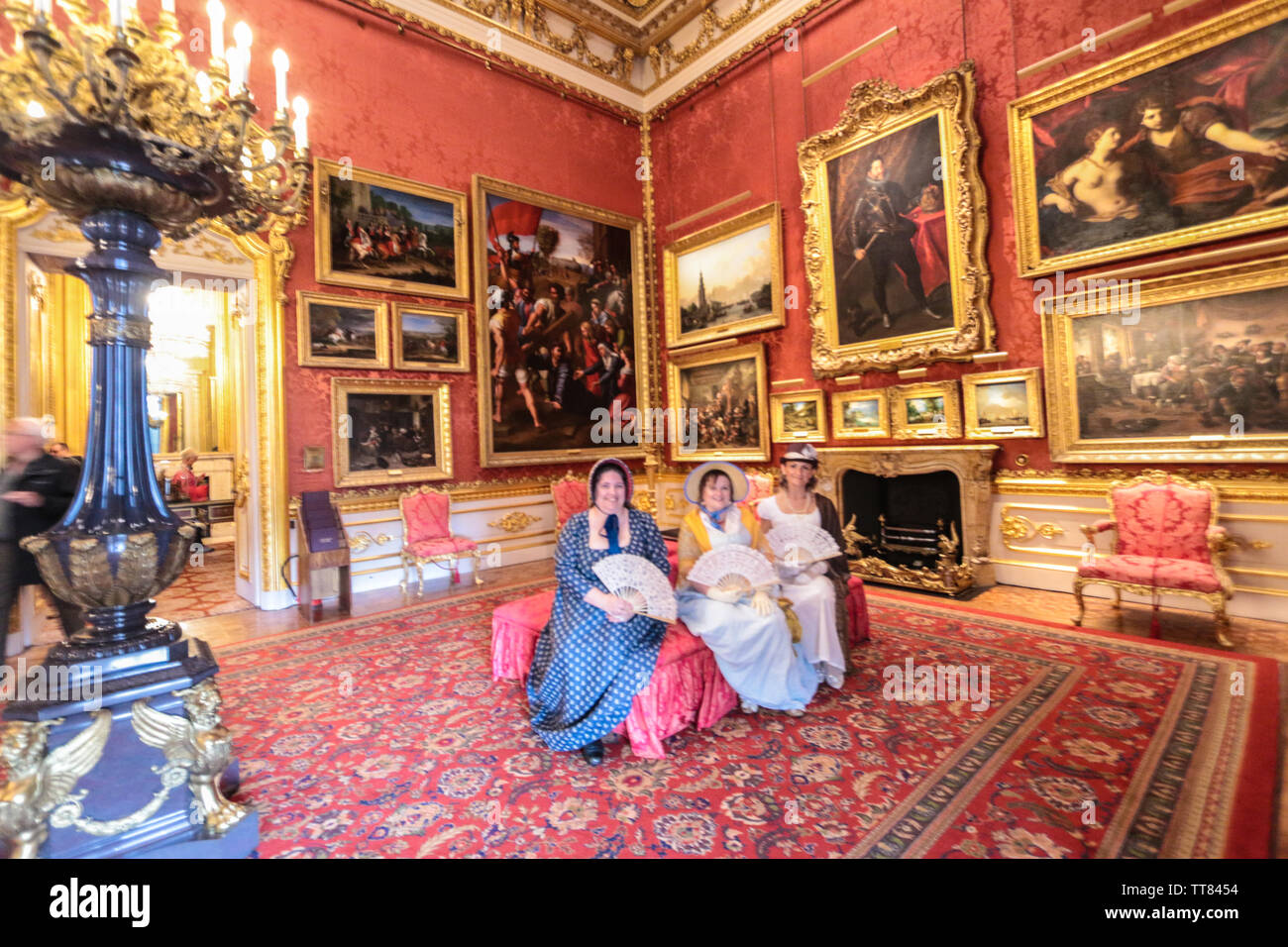 London, UK. 15 June 2019. Three Actresses in period costum in The Waterloo Gallery is the final element of Benjamin Dean Wyatt's work on Apsley House completed in 1830. The style is French revival and has been described as after Louis XIV, Louis XV or Louis XVI. In reality it is an eclectic mix which was a hallmark of Wyatt's work. The gallery is double height; there is no second floor or attic in this part of the house. When Wyatt's designs for York (now Lancaster) House were delayed in 1826 they were re-worked for Apsley House.Paul Quezada-Neiman/Alamy Live News Credit: Paul Quezada-Neiman/A - Stock Image