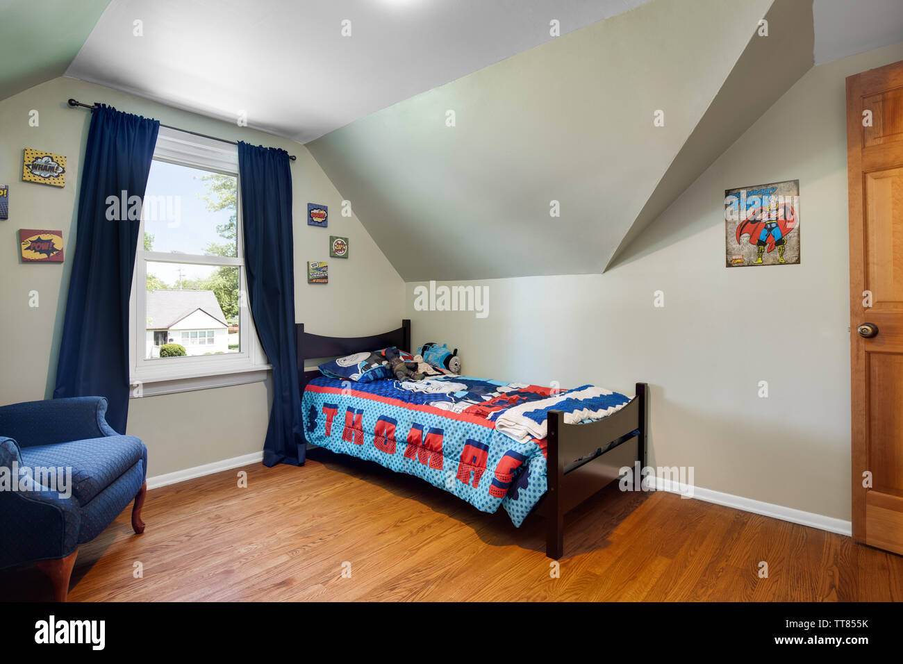 A young boy\'s room with a Thomas the Train bed set, a blue ...