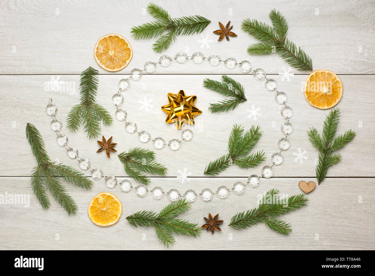Christmas spiral decoration with dried oranges, aniseed stars, fir tree branches and glass bead chain on white wooden background - Stock Image