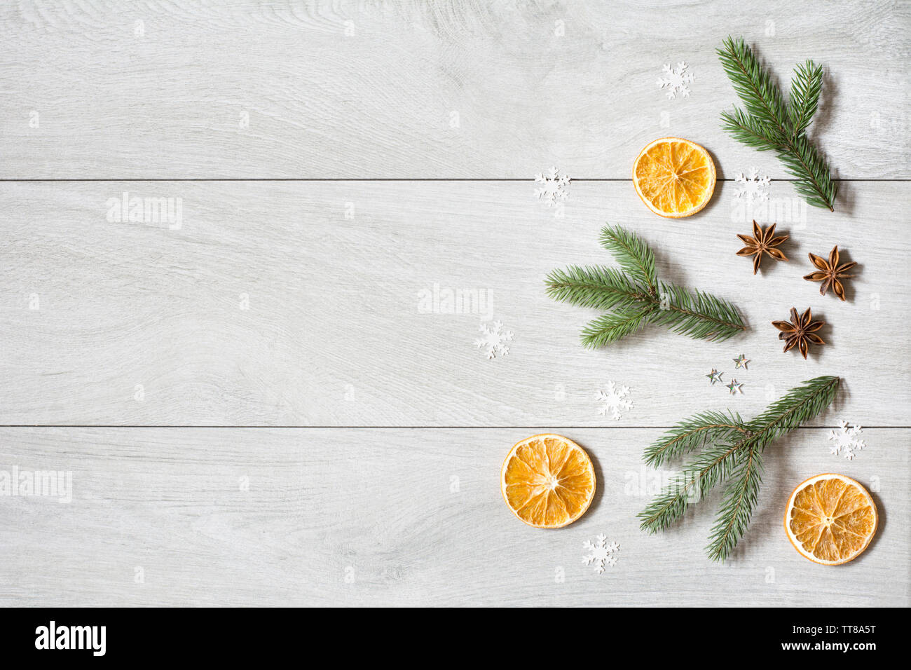 Christmas card with dried oranges, aniseed stars, fir tree branches and snow flakes on white wooden background - text space, deep shadows - Stock Image