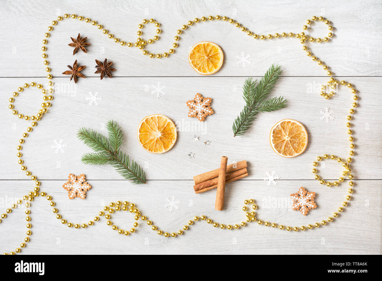 Christmas concept with dried oranges, aniseed stars, fir tree branches, snow flakes and golden bead chain on white wooden background - Stock Image