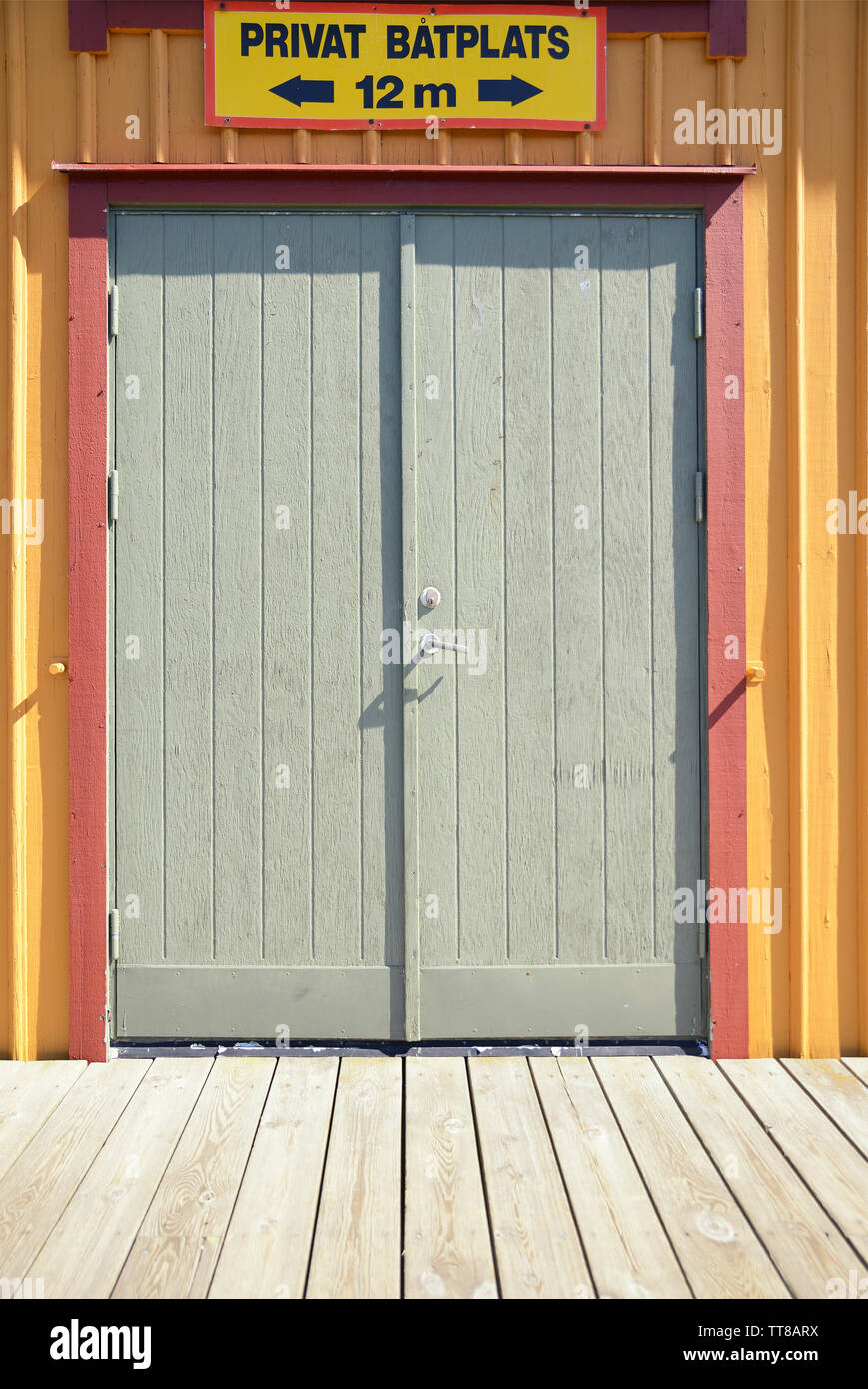 Old gray wooden garage door with Swedish prohibition sign - Stock Image