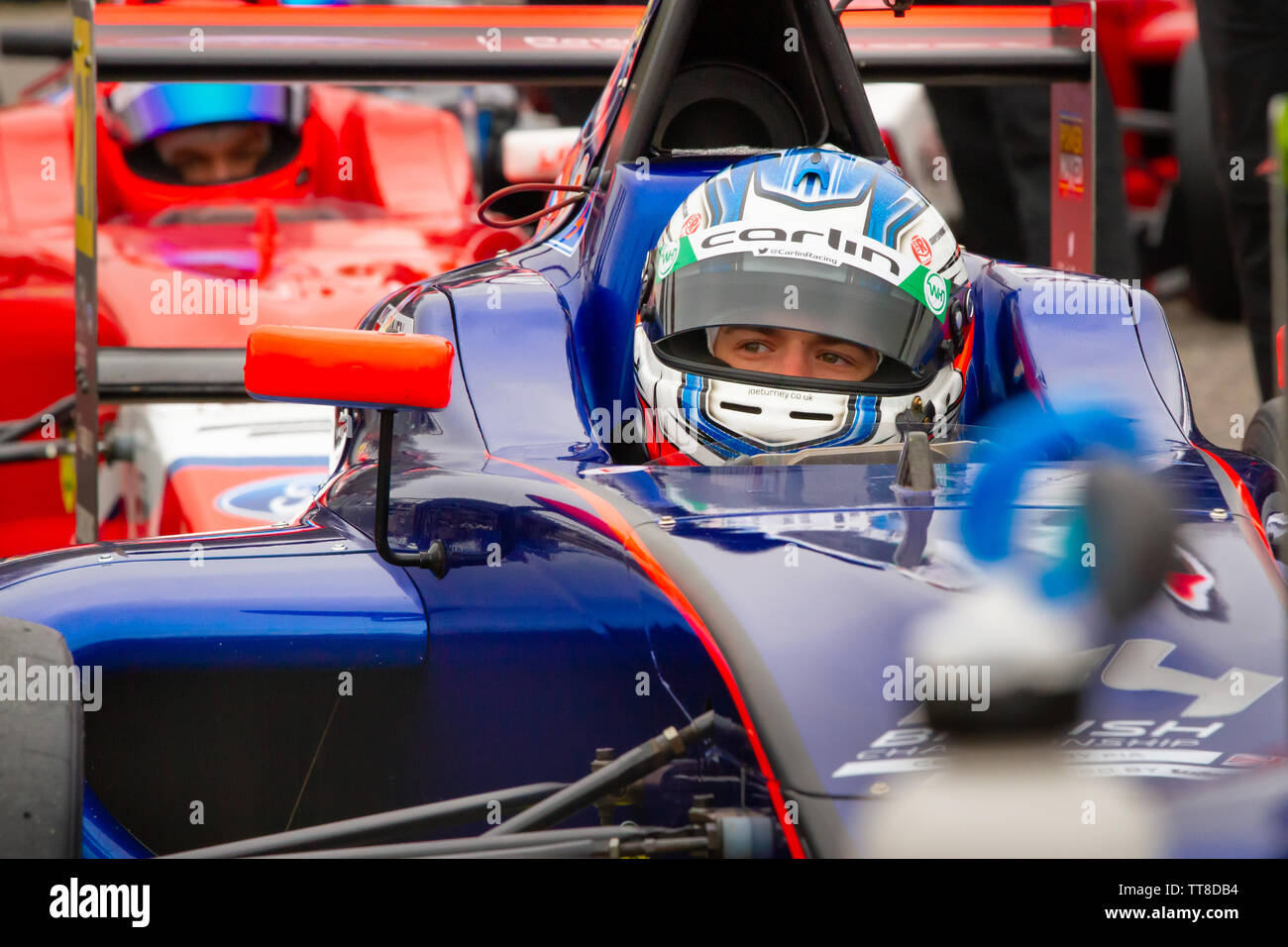 Joe Turney, British racing driver waits in his car. British Formula 4 paddock, prior to qualifying at Brands Hatch - Stock Image