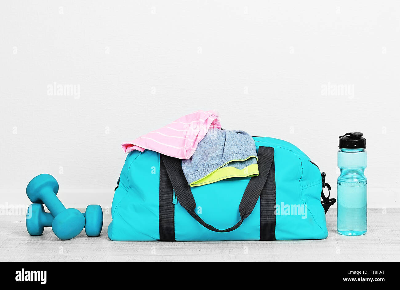Sports bag with sports equipment in room Stock Photo