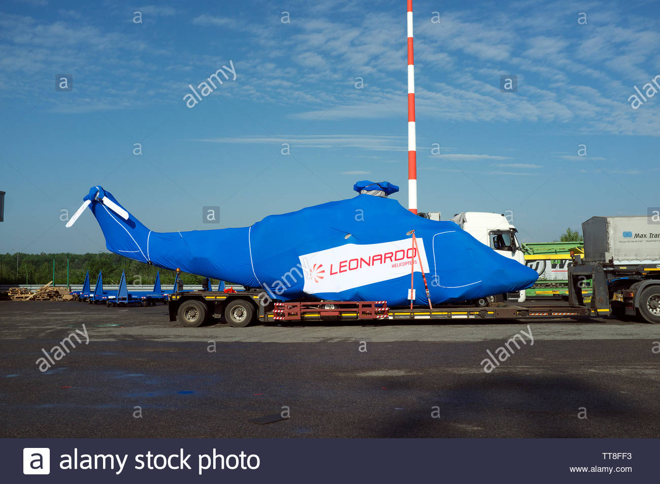A new Leonardo helicopter under protective sheeting, on the back of a low loader vehicle. Malpensa Airport, Milan, Italy. - Stock Image