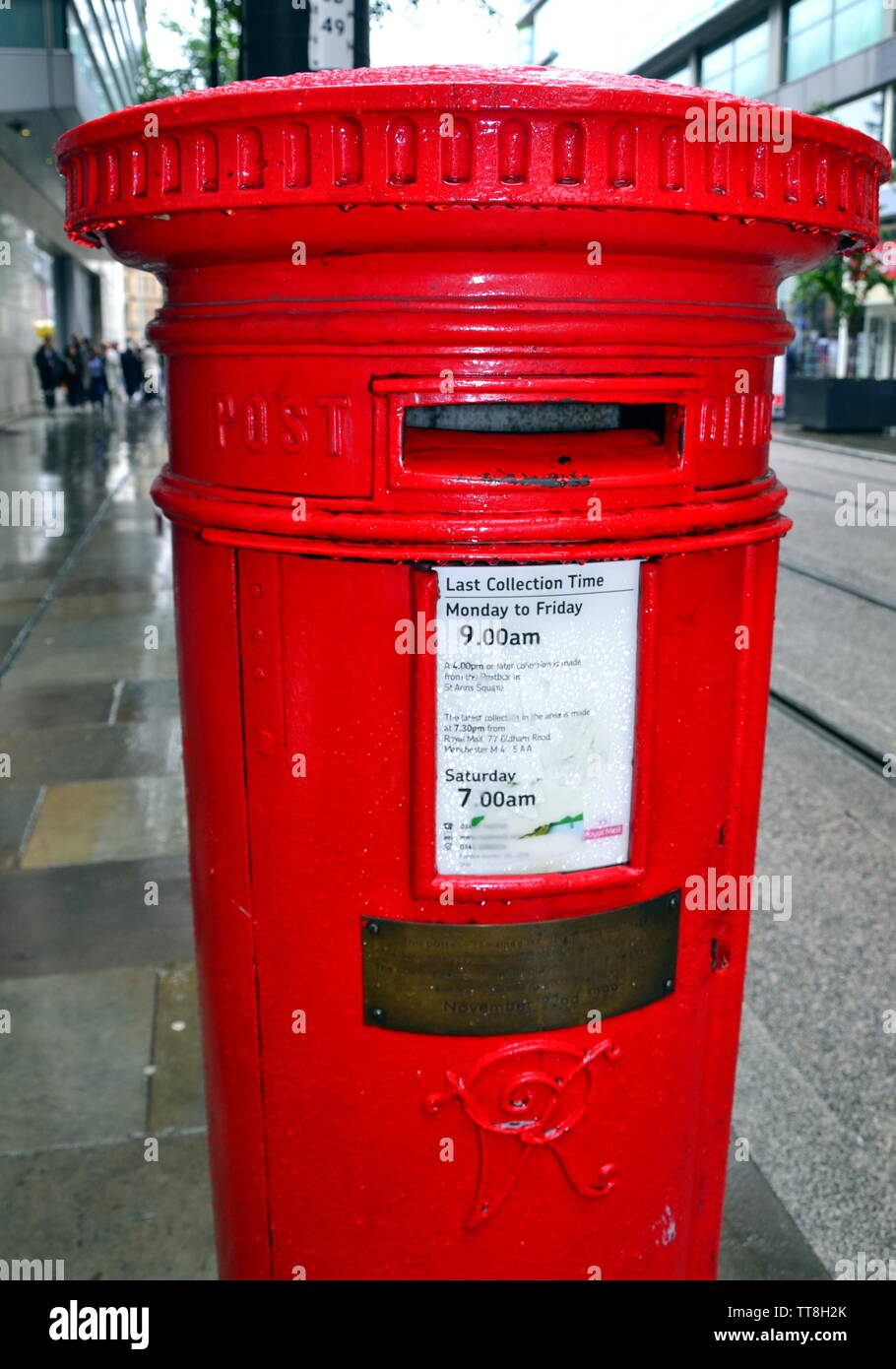 June 15, 2019, marks the 23rd anniversary of the IRA bomb which devastated the city centre of Manchester uk in 1996. This postbox on Corporation Street remained standing and bears a memorial plaque to mark this. The brass plaque carries the inscription: 'This postbox remained standing almost undamaged on June 15, 1996 when this area was devastated by a bomb. The box was removed during the rebuilding of the city centre and was returned to its original site on November 22nd 1999'. The bomb injured some 200 people. No-one has yet been charged with planting the bomb. - Stock Image