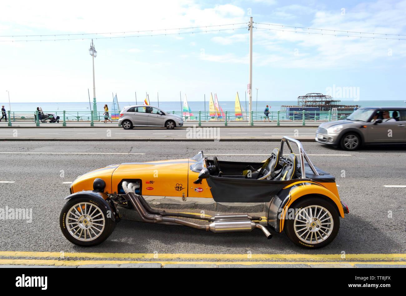 Brighton, UK - August 14, 2016: Beautiful yellow vintage Lotus Cobra car parked in the Brighton beach avenue with rests of Brighton's old West Pier. Stock Photo