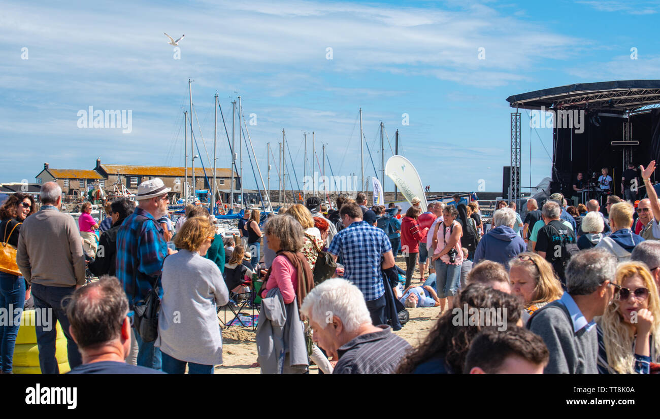 "Lyme Regis, Dorset, UK. 15th June, 2019. UK Weather: Crowds of musicians and visitors flock to the beach enjoy an afternoon of music as the annual Guitars on the Beach event gets underway on the beach at Lyme Regis on a glorious afternoon of warm sunshine and bright blue skies. The crowd is the star of the show as guitarists of all ages and abilities gather together on the beach perform together as 'Britain's biggest band'. People enjoy the laid back festival atmosphere before they perform this year's chosen song ""On the Beach"". Credit: Celia McMahon/Alamy Live News - Stock Image"