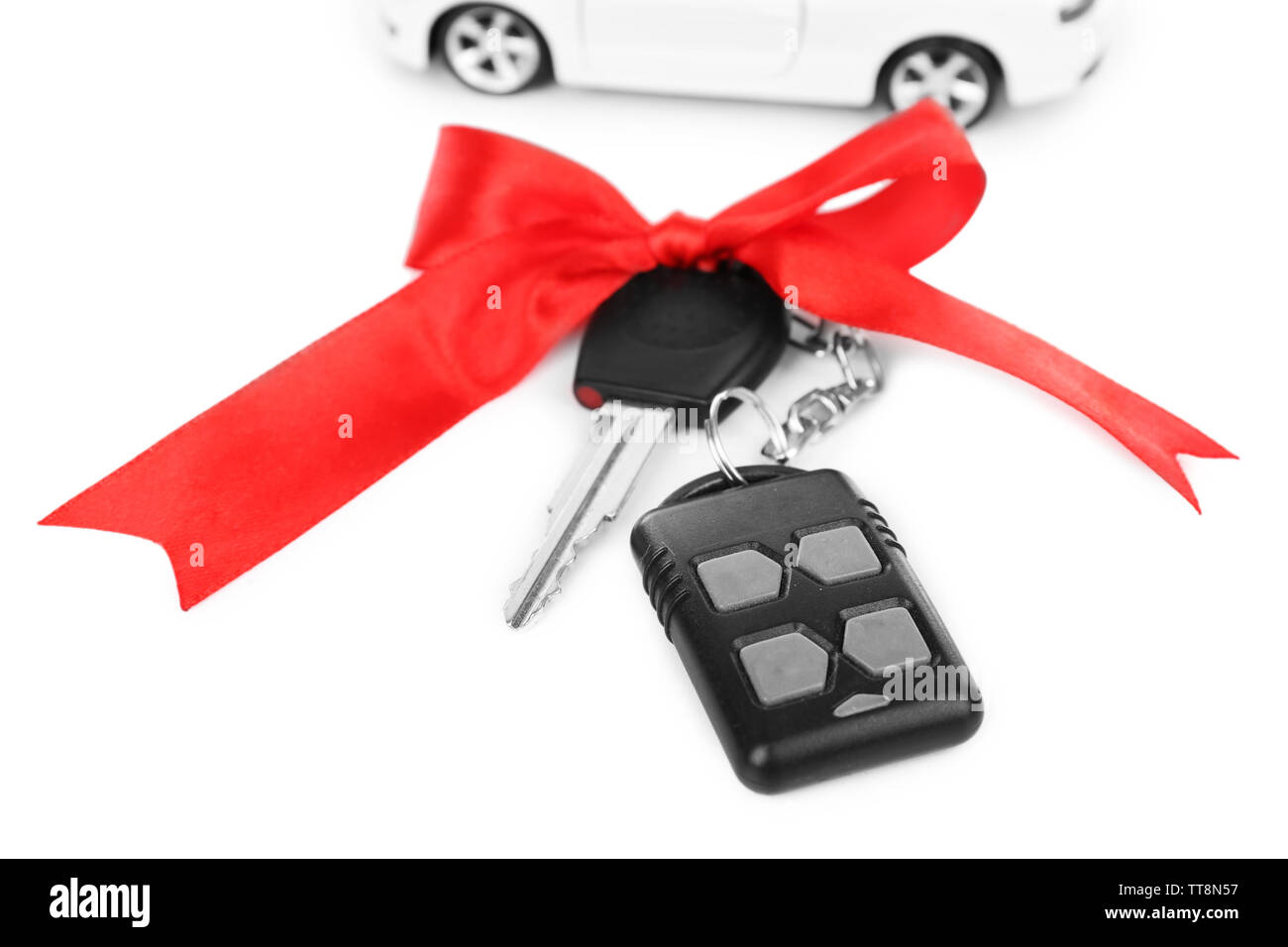 Keys with red bow and car as present isolated on white - Stock Image