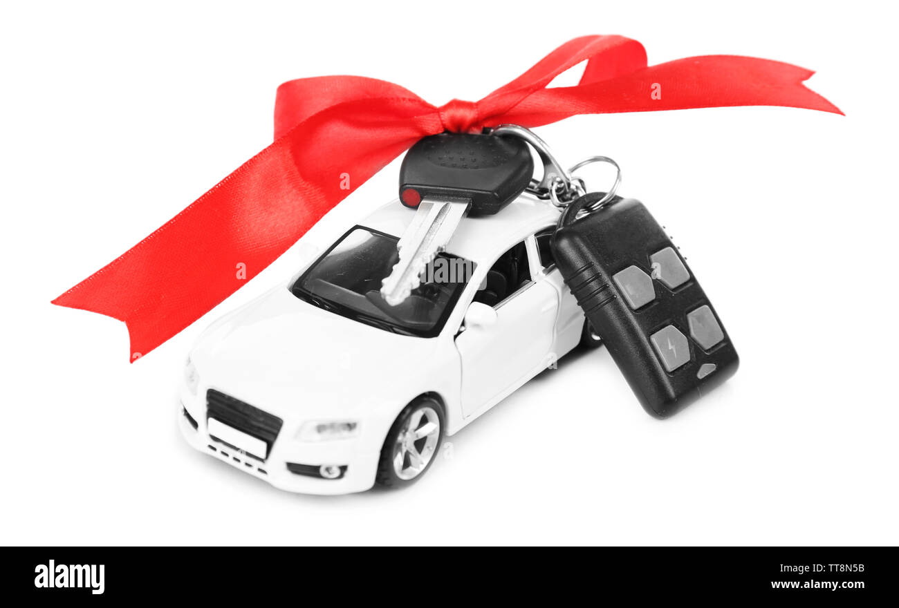 Keys with red bow on car as present isolated on white - Stock Image