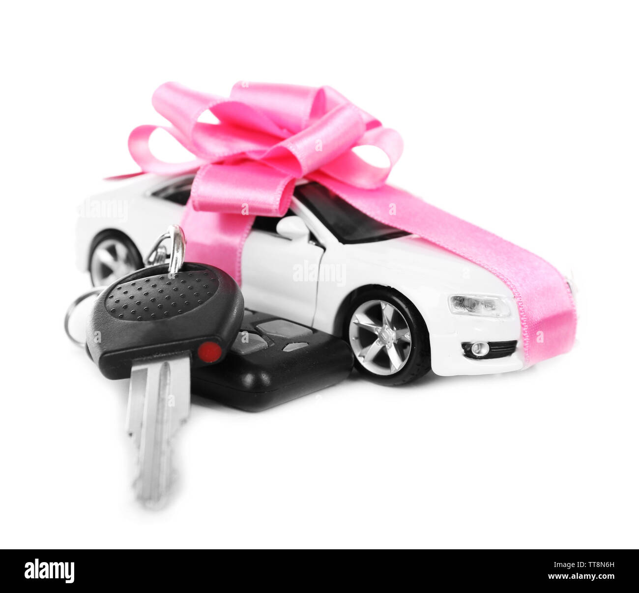 Keys and car with pink bow as present isolated on white - Stock Image