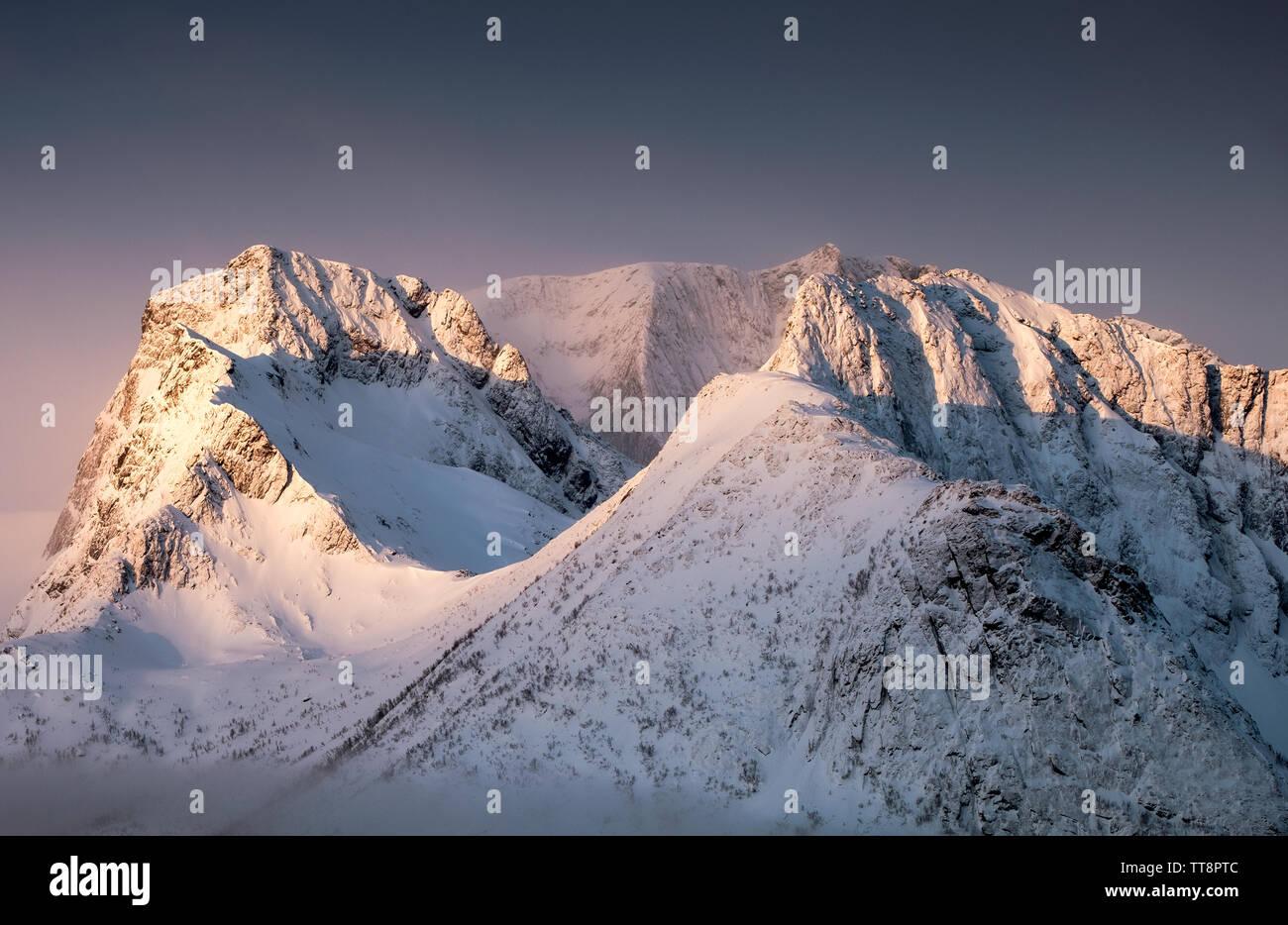 Golden light on snow peak hill in morning at Segla, Norway - Stock Image