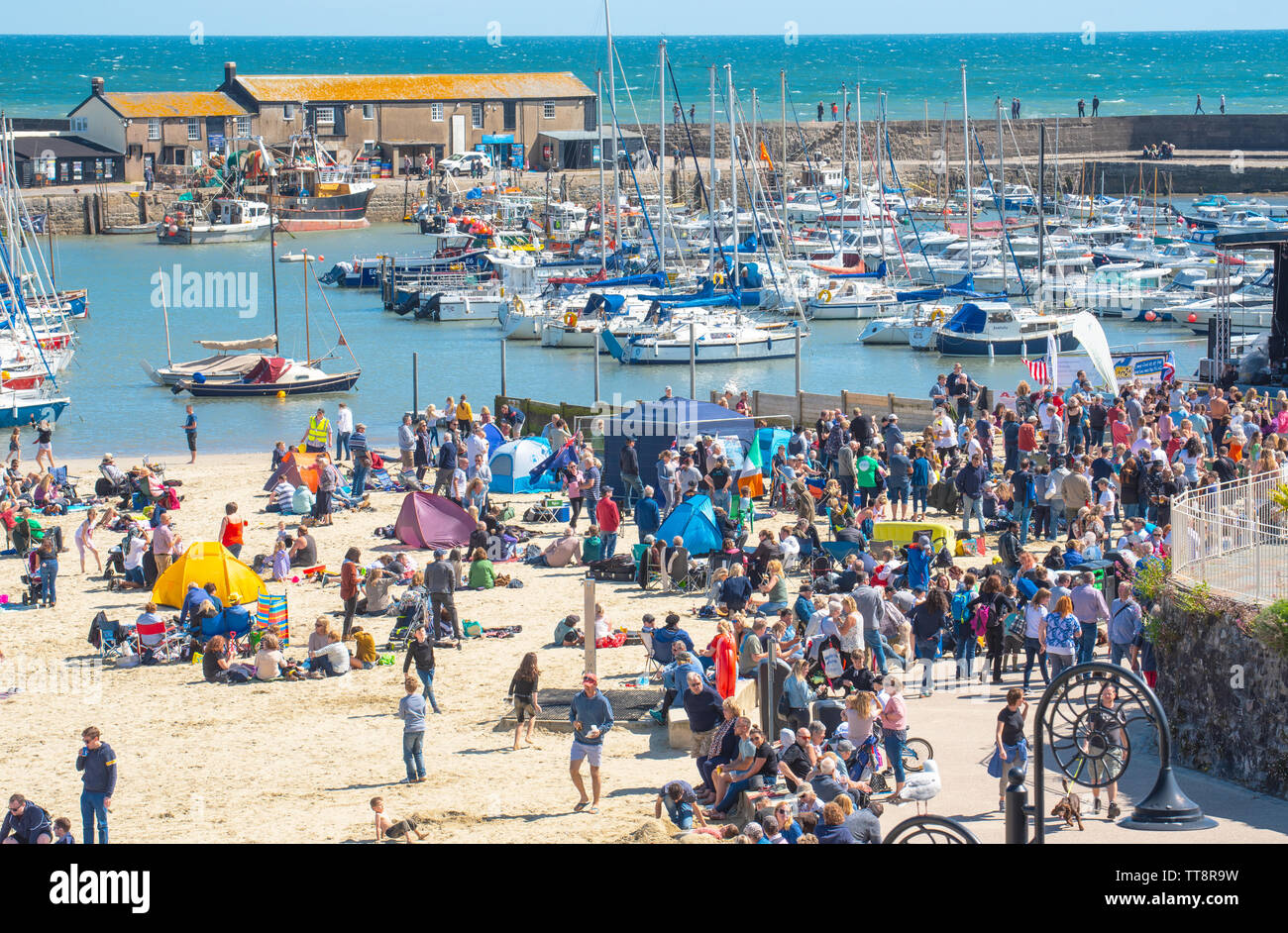 "Lyme Regis, Dorset, UK. 15th June 2019. UK Weather: Crowds of musicians and visitors flock to the beach enjoy an afternoon of music as the annual Guitars on the Beach event gets underway on the beach at  Lyme Regis on a glorious afternoon of warm sunshine and bright blue skies. The crowd is the star of the show as guitarists of all ages and abilities gather together on the beach perform together as 'Britain's biggest band'. People enjoy the laid back festival atmosphere before they perform this year's chosen song ""On the Beach"".  Credit: Celia McMahon/Alamy Live News. - Stock Image"