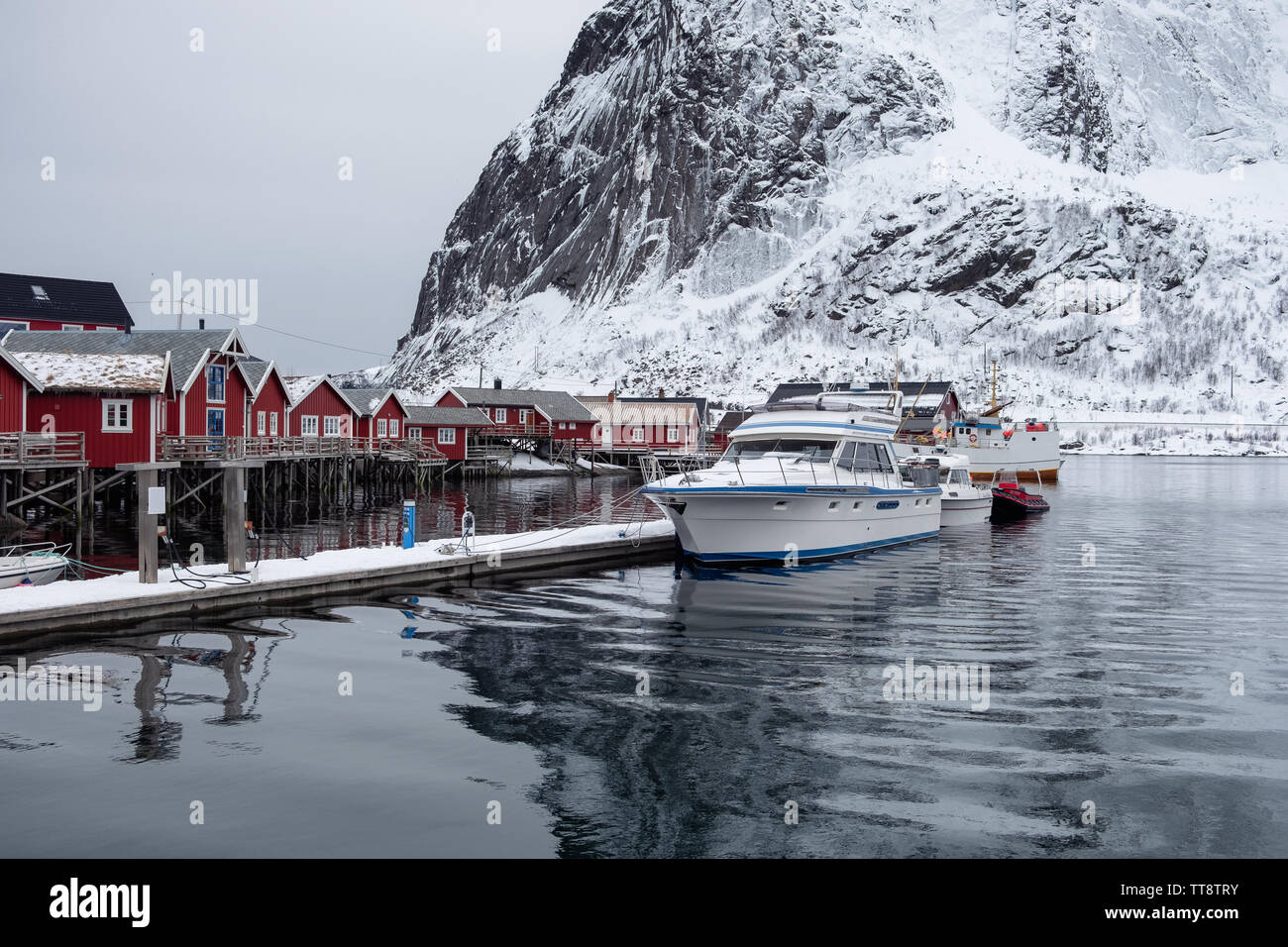 Boat anchored on pier with fishing village in Lofoten islands on winter - Stock Image