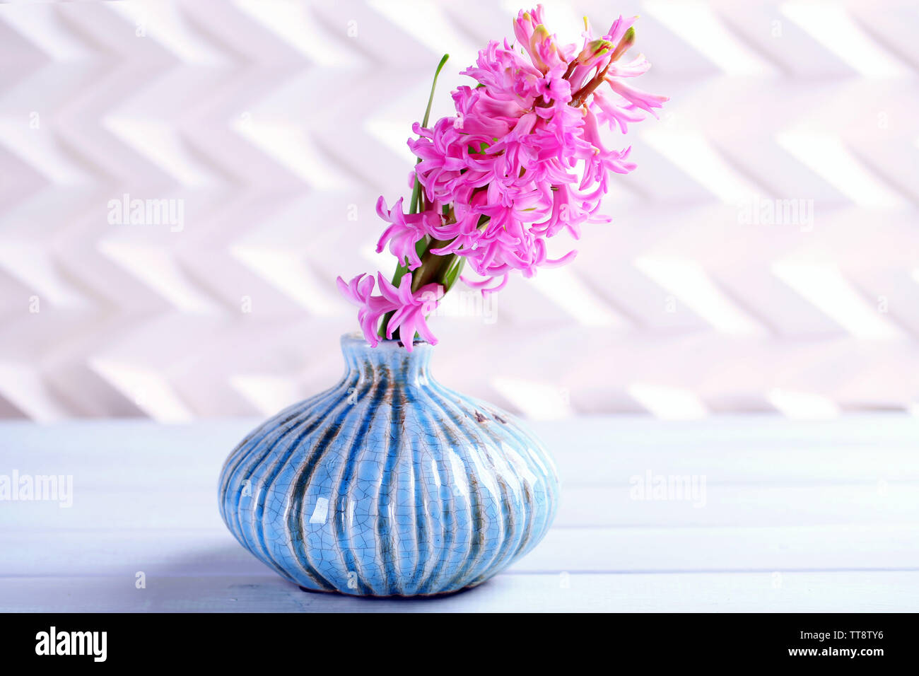 Beautiful hyacinth flower in vase on wooden table - Stock Image