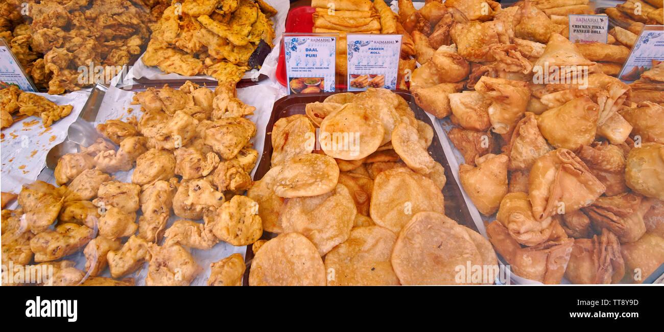 LONDON ENGLAND BRICK LANE INDIAN FOOD SHOP WINDOW WITH DELICIOUS VEGETABLE SAMOSAS CHICKEN TIKKA DAAL PURI PANEER AND CHANNA ROLLS - Stock Image