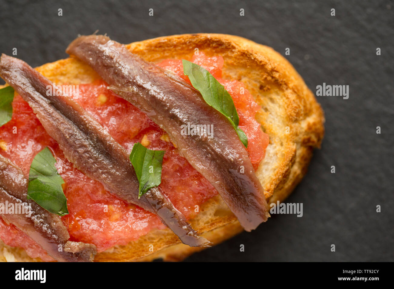 An example of Bruschetta which is an Italian dish comprising of grilled bread, olive oil and garlic with various toppings. In this case the bread has - Stock Image
