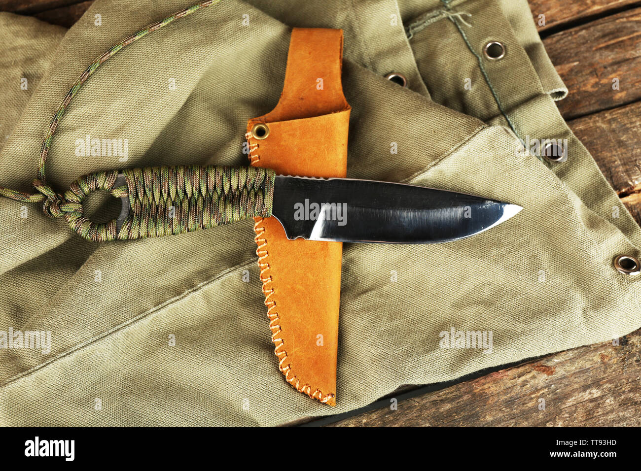 Hunting knife on wooden table with sackcloth, closeup - Stock Image