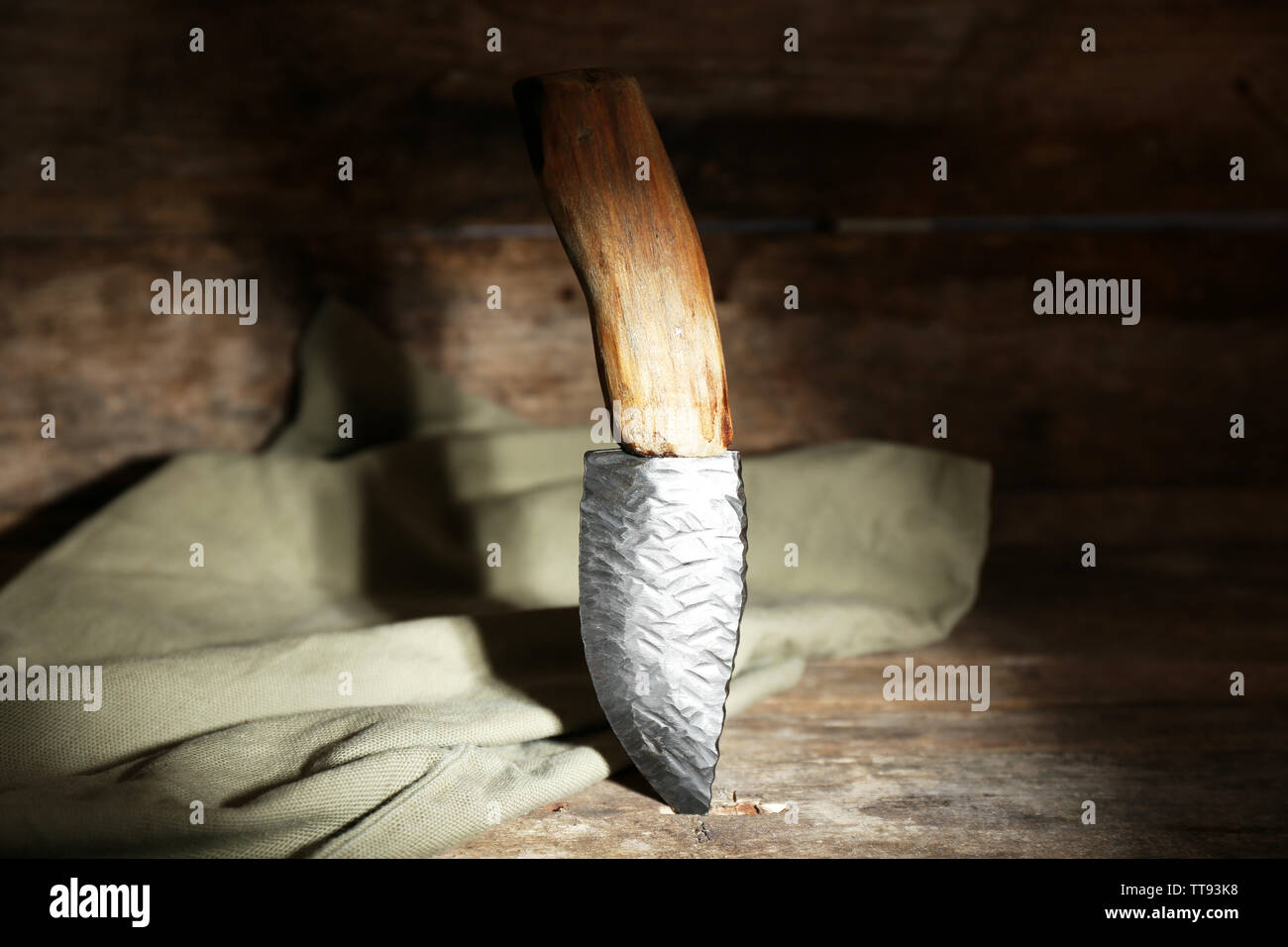 Hunting knife and sackcloth on wooden background - Stock Image