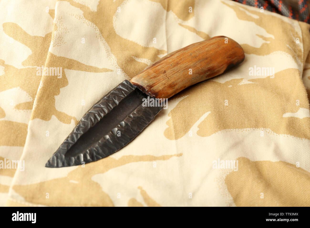 Hunting knife on military cloth, closeup - Stock Image