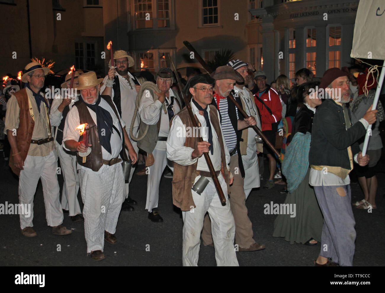 SIDMOUTH, DEVON, ENGLAND - AUGUST 10TH 2012: A group of men dressed as pirates take part in the night time closing procession of folk week. - Stock Image