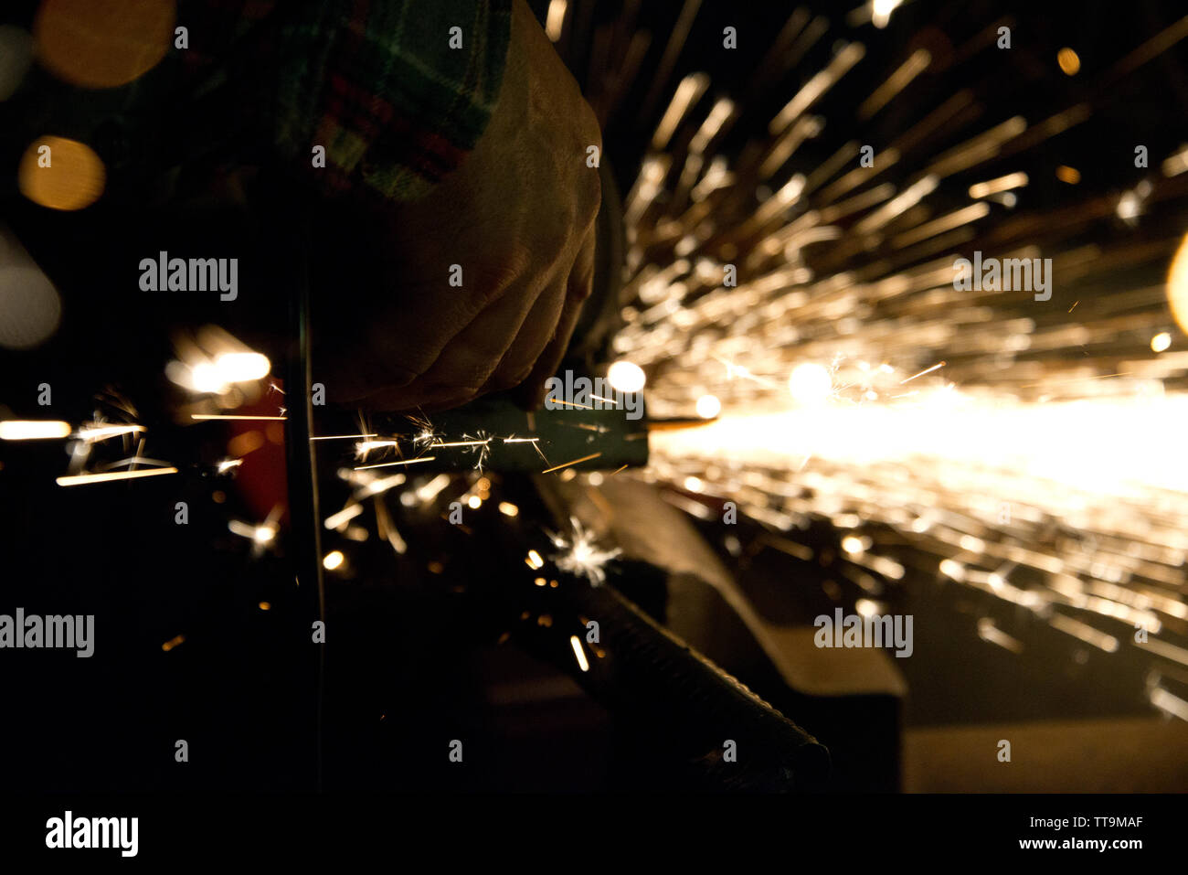cutting metal with angle grinder, producing rows of sparks, in smithery in franconia, Germany - Stock Image