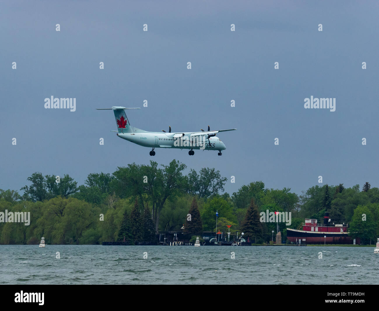 Air Canada Express De Havilland Canada DHC-8-400 flying in 33km/h or 20.5mph wind, past Centre Island on approach for landing on the island airport. - Stock Image