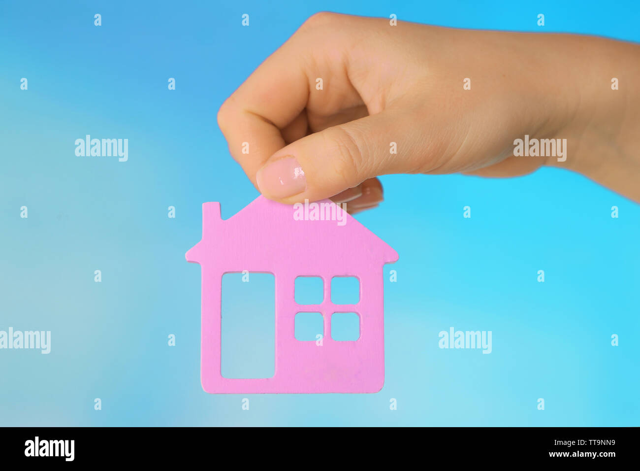 Female hand with model of house on color background - Stock Image