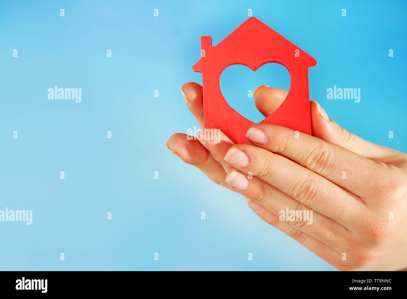 Female hands with model of house on color background - Stock Image