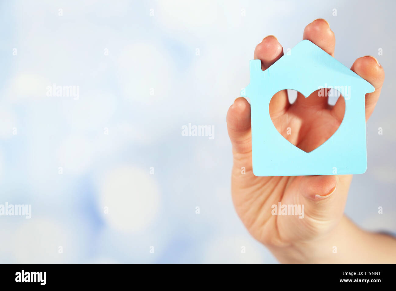 Female hand with model of house on blurred background - Stock Image