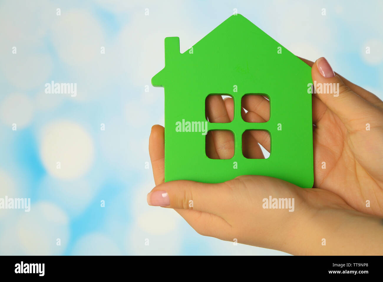 Female hands with model of house on blurred background - Stock Image