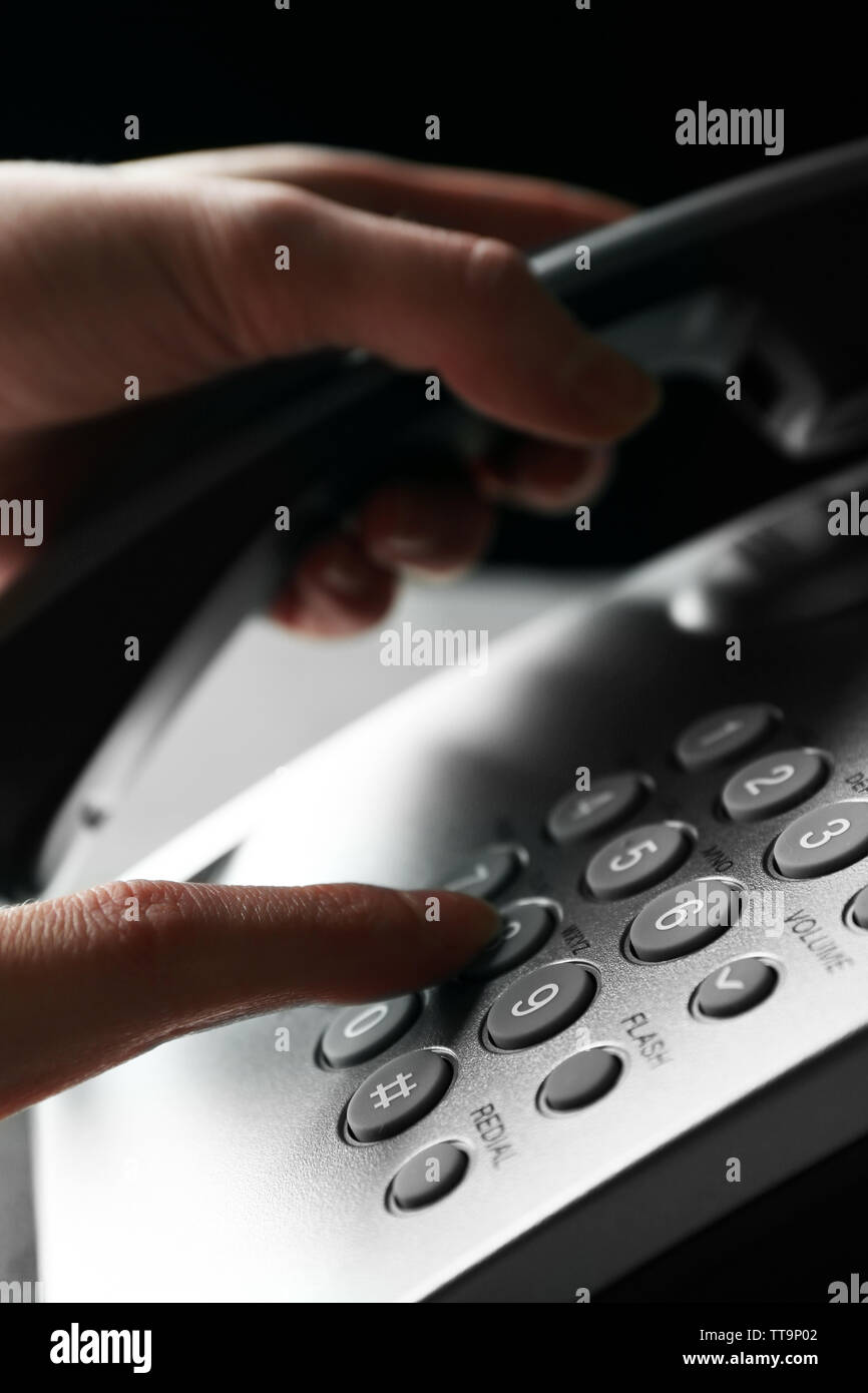 Finger pressing number button on telephone to make a call, close up - Stock Image
