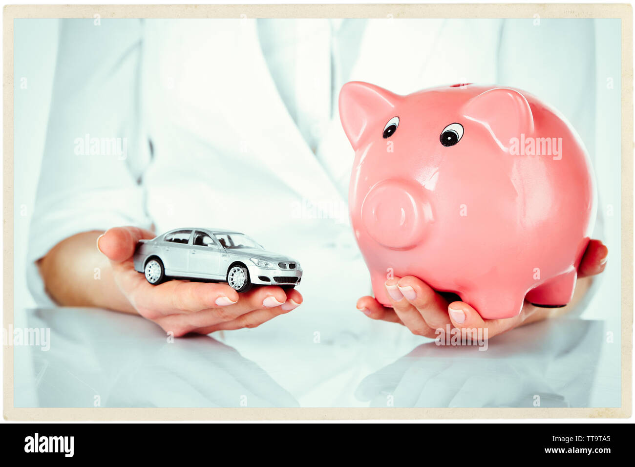 Woman holding model of car and piggy bank close up - Stock Image
