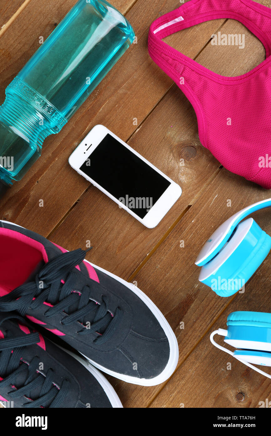 Sport shoes and clothes on wooden background - Stock Image