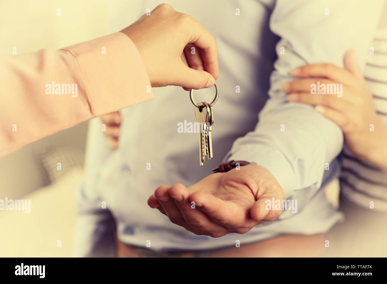 Real estate agent giving keys to young couple - Stock Image
