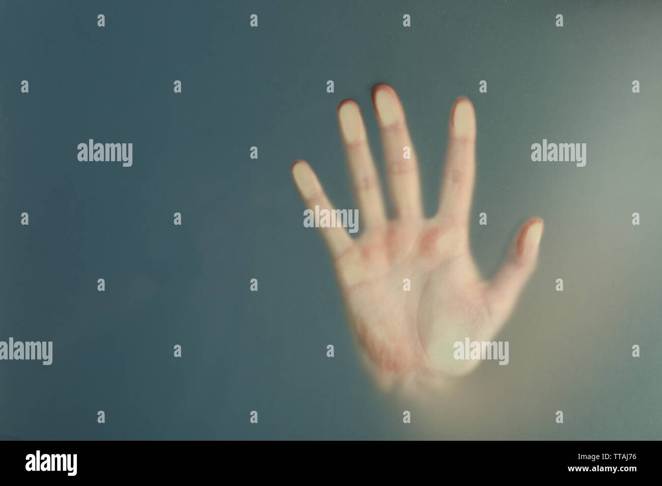 Female hand behind  wet glass, close-up - Stock Image