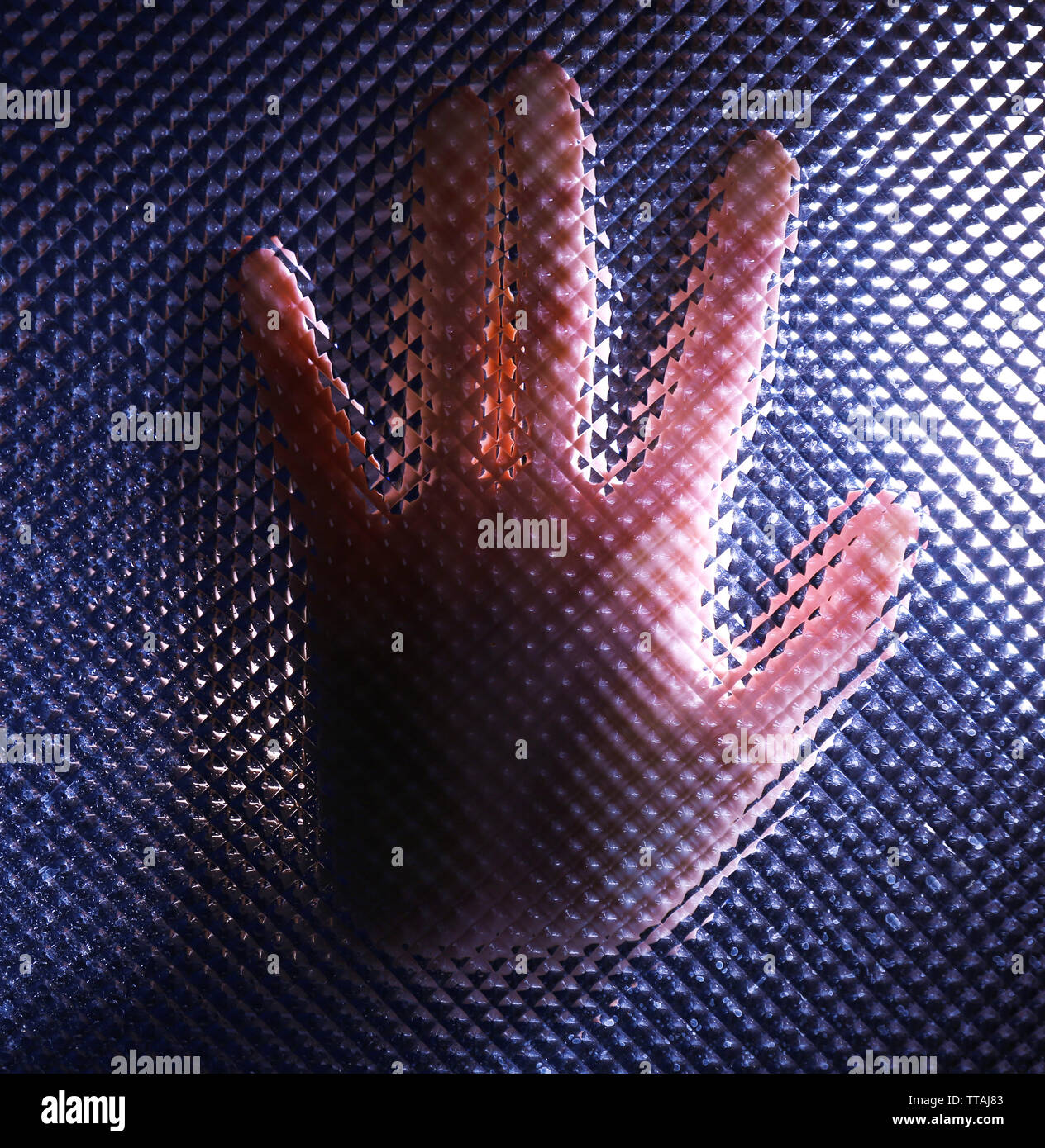 Female hand behind frosted glass, close-up - Stock Image