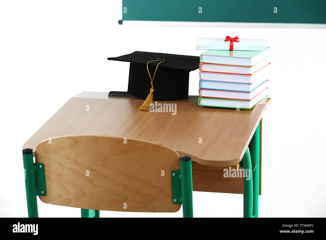 School desk with master hat, stack of books and diploma in classroom - Stock Image