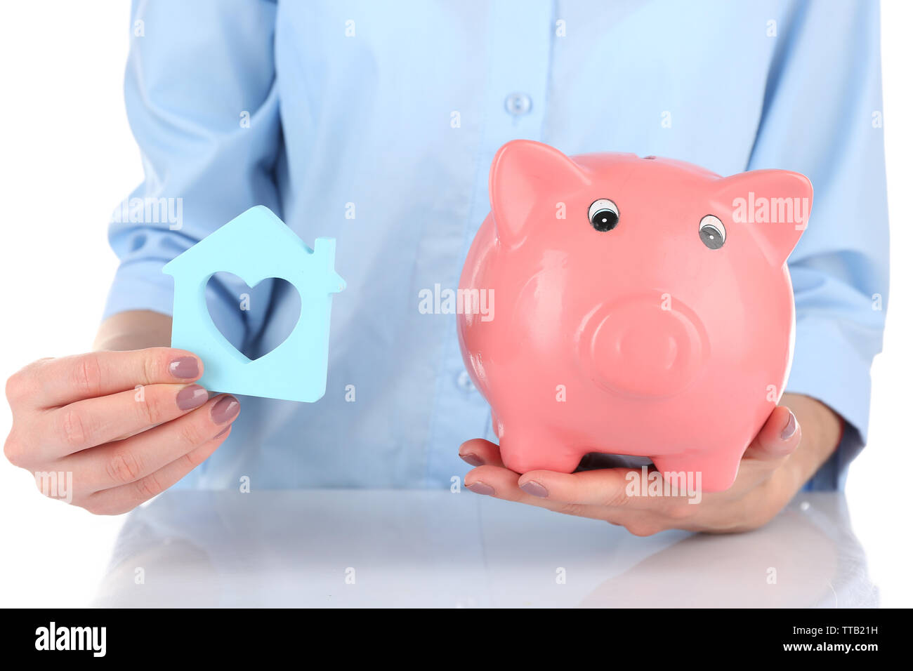 Female hands holding piggy bank and house, closeup - Stock Image
