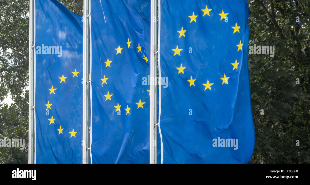 Hannover, Germany, May 26., 2019: Three flags of the European Union hanging from the mast and blowing in the wind - Stock Image